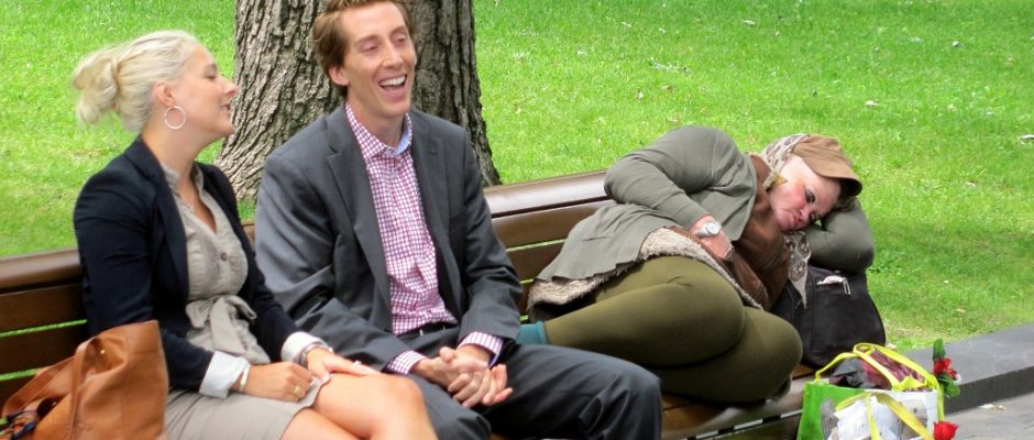 Prosperous couple & bag lady on a bench